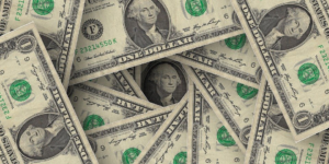 Stack of dollar bills scattered around